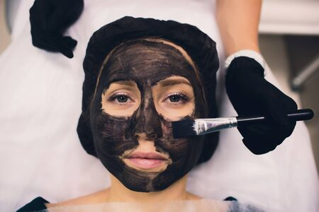 The cosmetologist in pink gloves with a brush applies a carbon mask for peeling on the face of a young girl in a cosmetology room. The concept of cosmetology services and self-care.