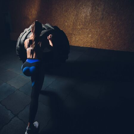 Fitness woman flipping wheel tire in gym. Fit female athlete working out with a huge tire. Back view. Sportswoman doing an strength exercise training.