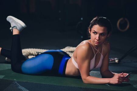 Fit young woman lying on exercise mat doing stomach exercises. Banco de Imagens