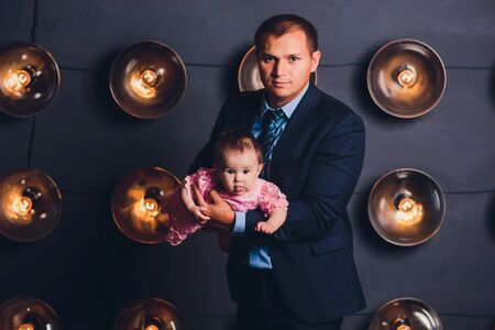 happy young father and his baby, against dark studio background.