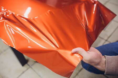 Car wrapping specialist putting vinyl foil or film car wrapping protective film yacht, boat, ship, car, mobile home. orange film heating with hair dryer and trimming plastic soft hard squeegee