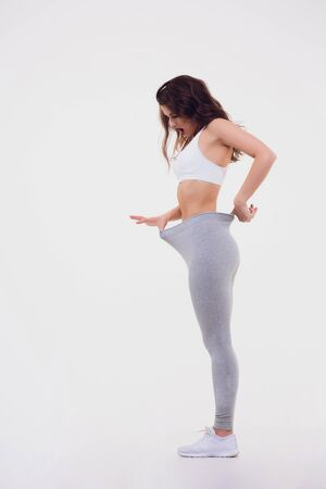 Happy woman after weight-loss is try her old jeans. Zdjęcie Seryjne