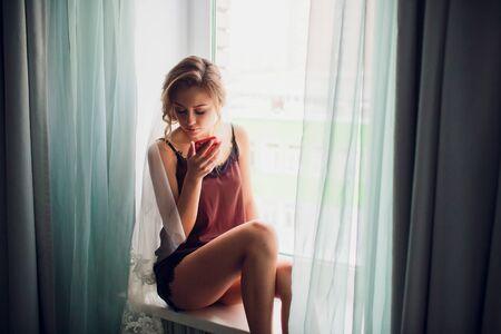 girl in a wedding veil near a window in a dark room Zdjęcie Seryjne