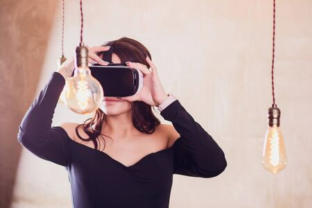 Girl use modern virtual reality glasses for mobile game application.Use mobile apps,play video games everywhere.Close up,focus on vr headset in woman hands.Trendy new augmented reality gaming device