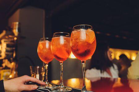 cocktail alcoolique tonique avec amer rouge, tonique, citron vert et glace. Vieux fond de table en bois, outils de bar, mise au point sélective. Tous les noms font référence à des cocktails, pas à des marques déposées.