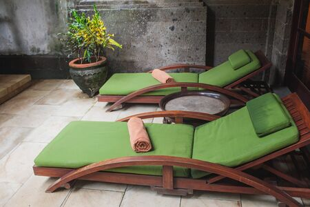 Wooden sunbeds next to a swimming pool in beautiful, green, Spanish garden on a sunny day. 版權商用圖片