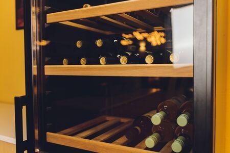 Wine bottles cooling in refrigerator Shelf close-up wood.
