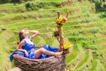 Beautiful young woman in blue silk dress. Girl travel and explore world. Typical Asian hillside with rice farming, mountain shape green cascade rice field terraces paddies. Ubud, Bali, Indonesia.