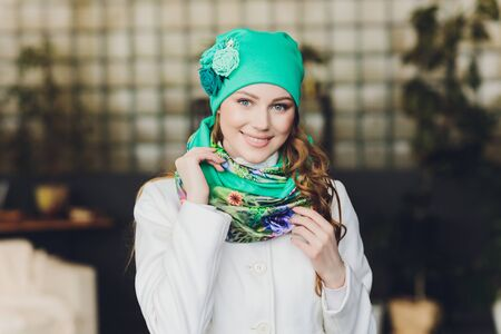 Surprised happy beautiful woman looking sideways in excitement. Christmas girl wearing knitted warm hat and mittens, isolated on gray background.