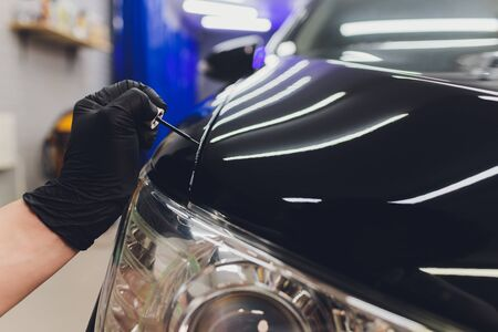 Car detailing - Man applies nano protective coating to the car. Selective focus
