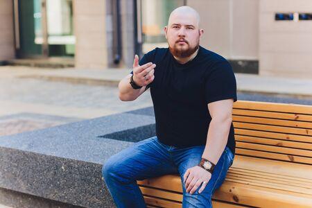 portrait d'un bel homme barbu chauve dans un t-shirt noir dans la rue, qui détourne le regard.