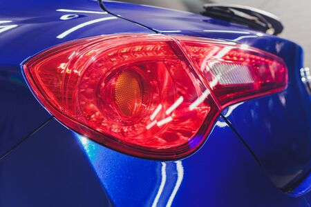 Red taillight of a modern car close-up. Service, repair, body repair, body painting, spare parts concept.
