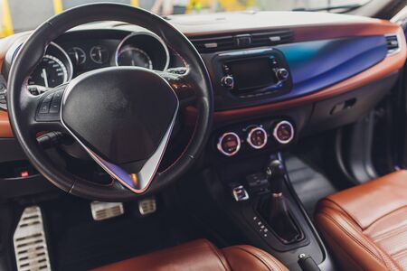 Dark luxury car Interior - steering wheel, shift lever and dashboard. Car interior luxury. Beige comfortable seats, steering wheel, dashboard, climate control, speedometer, display. Banque d'images