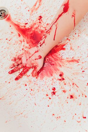 Bloody hand of depressed woman in shower.