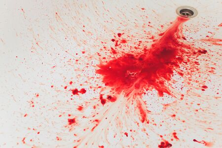 Fresh red blood splat on white porcelain with specks from the impact. Copy space area for horror themed concepts and ideas.
