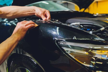 Transparent film, car paint protection, wrapping specialis. Car detailing. Selective focus. 免版税图像
