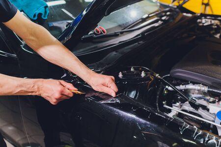 Transparent film, car paint protection, wrapping specialis. Car detailing. Selective focus. Foto de archivo