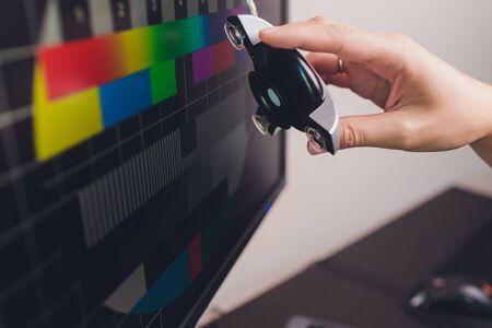 Fotografenmonitor mit Display-Kalibrierung im Büro, Tools zur Farbkalibrierung. Standard-Bild