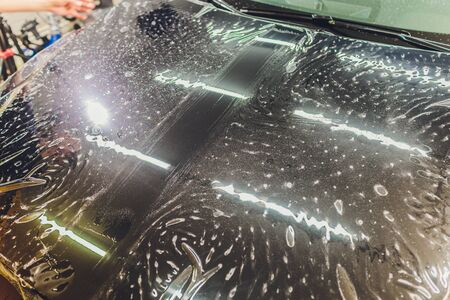Transparent film, car paint protection, wrapping specialis. Car detailing. Selective focus. Stock Photo