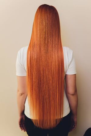 rear closeup view of the shoulders of red haired carrot-top female.