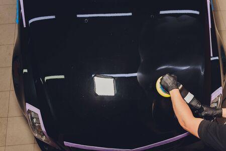Car detailing - Hands with orbital polisher in auto repair shop. Selective focus Standard-Bild