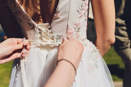 Bridesmaid is helping the bride to dress. Reklamní fotografie