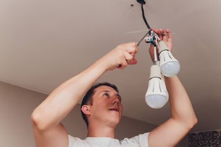 an electrician. repair work. Chandelier to hang on the ceiling. Banco de Imagens