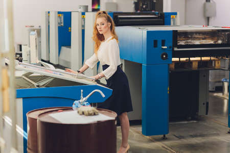 Young woman working in printing factory. Printing Press. Reklamní fotografie