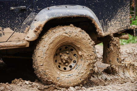 Wheel closeup in a countryside landscape with a muddy road.