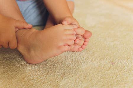 Childrens bare feet. Childs bare feet on the wooden floor. Imagens
