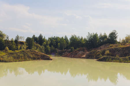 Open pit asbestos quarry lake with blue water.