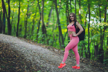 Young smiling woman hiker hiking mountain trail, walking on grassy hill, wearing backpack. Outdoor activity, tourism concept.