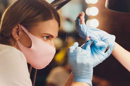 Close-up of beautician applying colorful varnish. Applying nail polish on nails with a brush for applying nail polish on fingers. Manicure nail applicator in a beauty salon. In a beauty salon varnish. Imagens - 152445258
