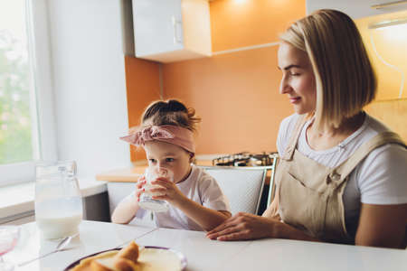 Portrait of an adorable mother and daughter preparing a daughter together in the kitchen.