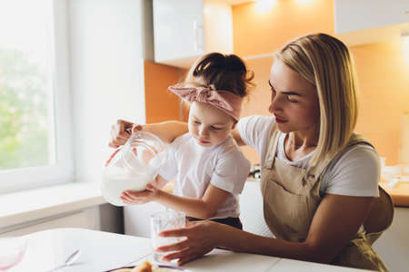 Portrait of an adorable mother and daughter preparing a daughter together in the kitchen. Imagens - 152449623