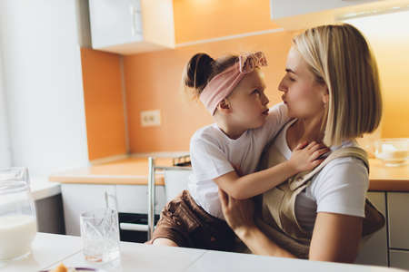 Portrait of an adorable mother and daughter preparing a daughter together in the kitchen. Imagens - 152449626