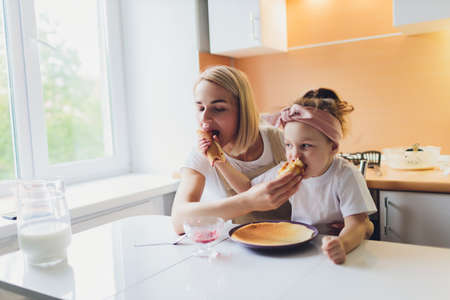 Portrait of an adorable mother and daughter preparing a daughter together in the kitchen. Imagens - 152449629