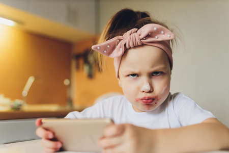 Girl eating at the table playing on the phone. Imagens