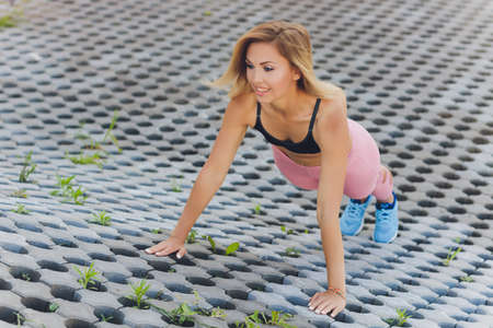 Attractive and strong woman stretching before fitness in the summer park. Sports concept. Healthy lifestyle. Banco de Imagens