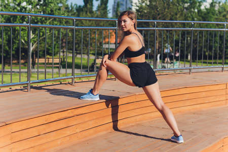 Young woman doing sport exercises outside with bench.