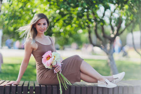 attractive woman sits o bouquet of peony flowers.