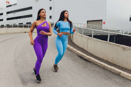 Two female athletes training racing running upstairs on city stairs in urban turf background.