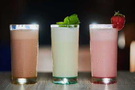 Three different colorful berry smoothies with twinkling party lights standing in a row on a rustic wooden counter top at a restaurant or bar. Banque d'images