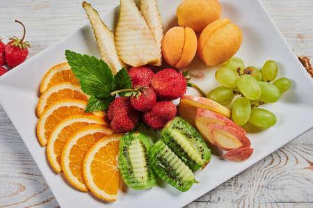 plate with fresh mixed fruits on white background. Zdjęcie Seryjne