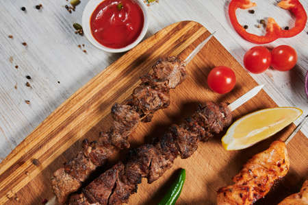lamb shish kebab with vegetables on a wooden Board. Stock Photo