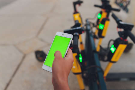 Electric urban transportation: the row of electric readies to ride scooter bikes with accumulators in the center of a city on the pavement stone with red electric bicycles behind