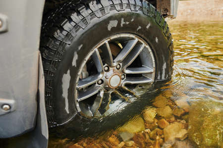 Four wheel drive agricultural vehicle crosses a flooded forded stream in nation park s forest. Archivio Fotografico