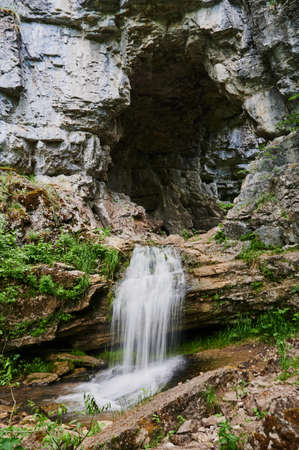 view of a small mountain river waterfall among large cobblestones from a cliff. Archivio Fotografico
