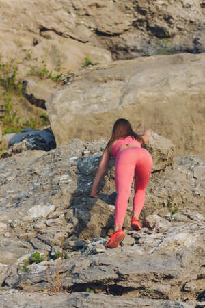 A young woman is engaged in rock climbing. Leisure and active sports. Light. Bottom view.