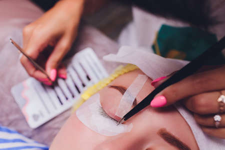 Bunch of artificial eyelashes in tweezers. Extensions of artificial eyelash, process close up. Woman in a beauty salon. Beauty and self-care.